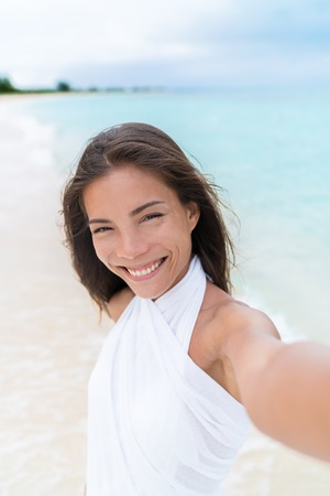 Selfie of beautiful Asian chinese caucasian mixed race woman on beach wearing white cover-up dress. Pretty young adult holding camera phone smiling during summer vacation caribbean travel.