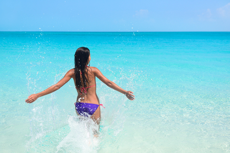 exhilarated: Young woman enjoying herself in sea during summer holidays. Exhilarated female is in bikini. Tourist with arms outstretched is on her vacation at beach.
