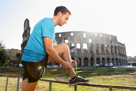 young male: Young male jogger running tying shoelace against Colosseum. Side view of runner preparing for workout on sunny day. Athletic man is in sportswear.