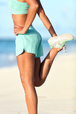 Female runner doing a standing quadricep front thigh stretch stretching exercise on her legs for running warm-up before workout on sunny beach. Lower body leg closeup of fitness athlete woman.