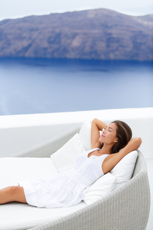 seaside resort: Beautiful young woman relaxing on couch at seaside resort terrace. Attractive female is wearing white sundress. Female with hands behind head is relaxing on lounge chair against sea and mountain. Stock Photo