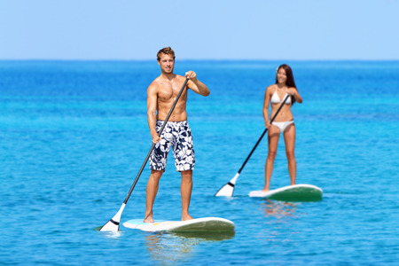watersport: Man and woman stand up paddleboarding on ocean. Young couple are doing watersport on sea. Male and female tourists are in swimwear during summer vacation. Stock Photo