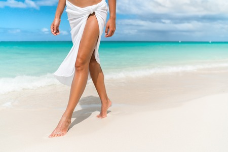 Caribbean vacation travel - woman leg closeup walking on white sand relaxing in beach cover-up pareo beachwear. Sexy lean and tanned legs. Sunmmer holidays, weight loss or epilation concept. Stock Photo