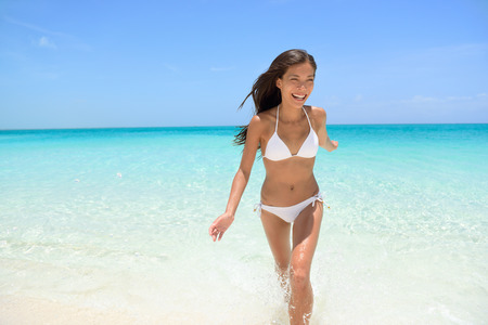 exhilarated: Cheerful young woman running on beach having fun laughing during summer holidays travel. Exhilarated female is in white bikini smiling. Beautiful tourist is enjoying vacation on beach. Stock Photo