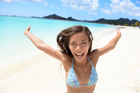 exhilarated: Exhilarated young woman screaming on beach. Portrait of cheerful female in bikini enjoying her summer vacation. Attractive tourist is standing with arms outstretched in nature.