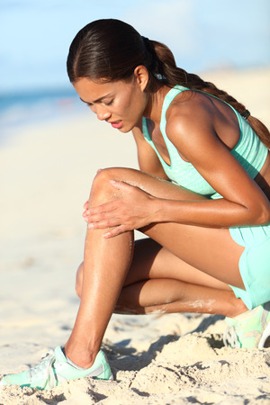 Runner injury - running woman upset with hurting knee pain. Asian female athlete with painful legs holding her leg in ache because of sport problem. Sporty girl jogging on beach.