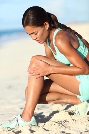 Runner letsel - lopende vrouw boos op het kwetsen van pijn in de knie. Aziatische vrouwelijke atleet met pijnlijke benen met haar been in pijn als gevolg van sport probleem. Sportief meisje joggen op het strand. Stockfoto
