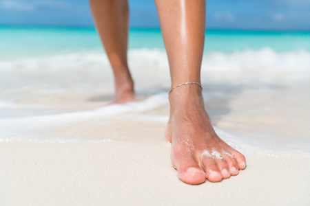 Beach feet closeup - barefoot woman walking in ocean water waves. Female young adult legs and toes wearing an ankle bracelet anklet relaxing in summer vacation travel.