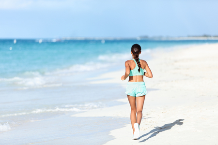 mindfulness: Sporty runner in running outfit training cardio jogging on sunny beach. Unrecognizable person exercising legs and body on white sand next to ocean waves.