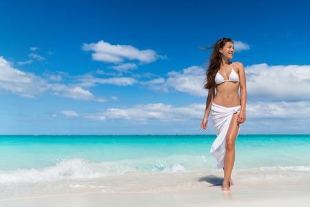 패션 비치웨어 흰색 은색 스커트 의류에 비치 여자. 태양 보호 여름 휴가 여행에 바다 물에 걸어 편안 하 게 흰색 pareo를 착용하는 아시아 소녀 관광.