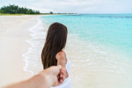 cogidos de la mano: Pareja de viajes de vacaciones de verano - Mujer que recorre en unas vacaciones románticas playa de luna de miel que llevan a cabo la mano del novio tras ella, vista desde atrás. Punto de vista. Foto de archivo