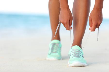 러너 여자 해변 조깅을 준비하고 실행 신발 끈을 매는. 심장 운동에 대한 크로스 트레이닝 운동화 트레이너 레이싱 손의 근접 촬영입니다. 적합하고 활 스톡 콘텐츠