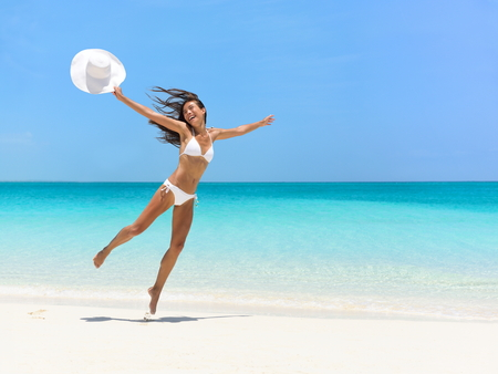 exhilarated: Carefree young woman jumping at beach during summer vacation. Full length of exhilarated female in white bikini. Tourist with arms outstretched is enjoying holidays on sea.