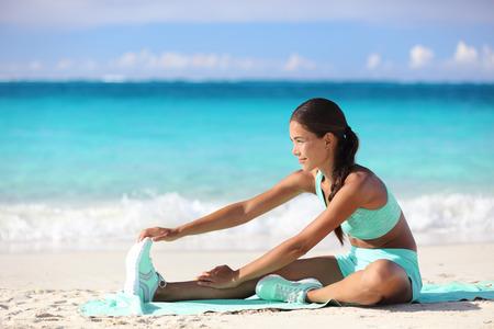 piernas: Mujer de la aptitud que estira las piernas en la playa - muchacha asi�tica deportiva que hace estiramiento de piernas, sentado estiramiento isquiotibiales con una sola pierna. joven adulto feliz de entrenamiento de la fuerza en el soleado de verano viajes playa tropical. Foto de archivo