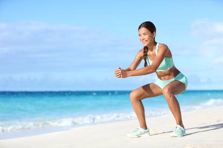 girl squatting: Fitness young woman working out core and glutes with bodyweight workout doing squat exercises on beach. Asian sporty girl squatting legs as part of an active and fit life.