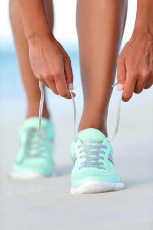 working woman: Sportswoman runner getting ready tying running shoes on beach. Fitness woman living a healthy and active life preparing for cardio training. Wellness and health concept.