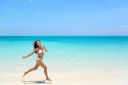 exhilarated: Carefree young woman with arms outstretched jumping on sea shore during summer. Full length of exhilarated female in white bikini. Tourist is enjoying vacation during summer.