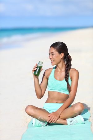 cleanse: Fitness woman drinking a healthy green smoothie juice for a detox weight loss cleanse. Happy sporty asian girl  on beach taking a snack break with a vegan beverage for a vegetarian diet. Stock Photo
