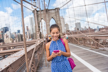 american media: Happy Asian woman using phone texting walking on Brooklyn bridge, New York city for social media or blogging. Tourist doing summer travel in Manhattan, USA.
