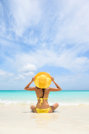 yellow bikini: Beach Travel Vacation Holidays Woman Relaxing. Woman sitting on sea shore during summer. Rear view of female wearing yellow sunhat and bikini. Carefree tourist is enjoying vacation at beach.