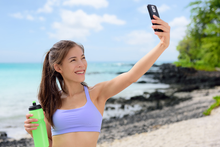 water sports: Smiling sporty woman taking selfie using smartphone on beach. Beautiful fit fitness female in sports bra is holding water bottle. Attractive young woman is posing at sea shore.