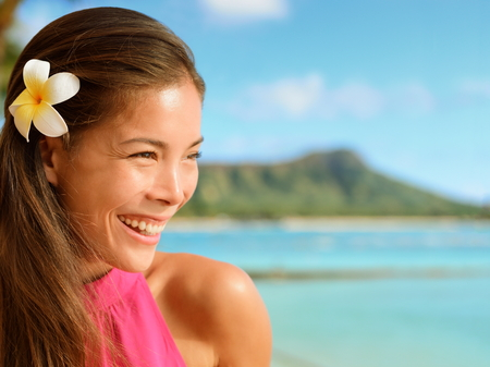 woman beach: Happy young woman looking away at beach. Attractive female is with frangipani flower in her hair. Beautiful tourist is enjoying her vacation. Stock Photo
