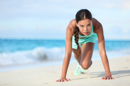 asian abs: Fitness athlete working out body core with bodyweight exercises. Strong fit woman training cardio and exercising abdominal muscles with mountain climber workout exercise on beach.
