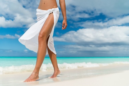 White pareo woman legs walking on tropical beach vacation. Closeup of barefoot female young adult lower body relaxing in ocean water on summer holiday travel wearing cover-up beachwear.