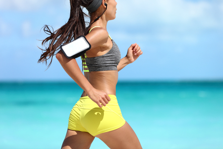 armband: Sports phone armband fitness jogger exercising on beach - cardio workout. Midsection closeup of female athlete runner jogging wearing smartphone sleeve and earphones. Glutes training. Stock Photo