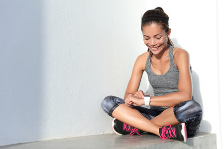 fille de remise en forme en utilisant l'activité traqueur smartwatch comme moniteur de fréquence cardiaque pour l'entraînement ou le suivi de son amélioration de la perte de poids. Femme coureur vivre une vie saine. technologie Wearable.