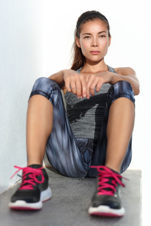 activewear: Fitness woman fit athlete relaxing sitting in outdoor gym in fashion running leggings sportswear thinking. Mindfulness concept. Asian runner taking a break from strength training workout. Stock Photo