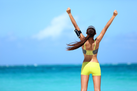 fitness goal: Strong fitness athlete arms up in success on summer beach after cardio training workout. Female runner woman running winning reaching goal achievement during strength training showing power.