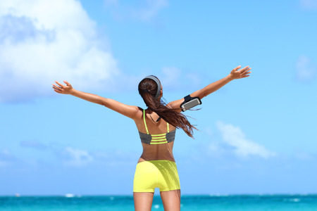 summer beach: Winning carefree woman runner expressing happiness on beach summer vacation. Back view of happy female athlete showing freedom and success from fitness goal achievement. Weight loss concept.