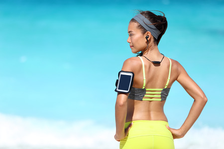 headphones: Fitness runner woman with fit back wearing phone armband and wireless headphones on ocean background. Multiracial exercise girl jogging on summer beach with sports smartphone touchscreen for app. Stock Photo