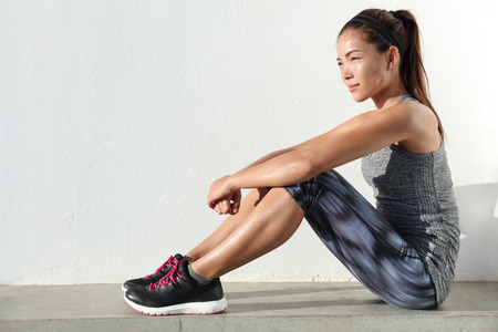 Fit Asian woman living a healthy and active lifestyle sitting and relaxing in fashion leggings, running shoes and grey fitness activewear outfit.