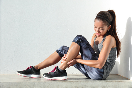Running injury leg accident- sport woman runner hurting holding painful sprained ankle in pain. Female athlete with joint or muscle soreness and problem feeling ache in her lower body. Foto de archivo