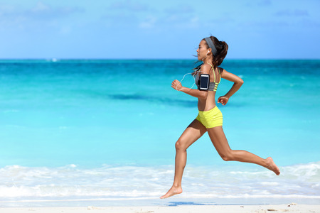 run woman: Fitness runner woman running on beach listening to music motivation with phone case sport armband strap. Sporty athlete training cardio barefoot with determination under summer sun. Stock Photo