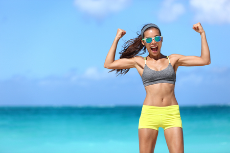 funny glasses: Strong fitness funny woman in neon blue wayfarer sunglasses on beach showing off muscular arms flexing biceps for fun. Fit girl in sportswear after running strength training workout winning in power.