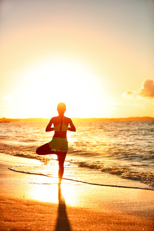 vriksasana: Meditation woman practicing Vriksasana tree yoga pose on beach at sunset. Serene young adult silhouette in morning sun flare balancing meditating doing a body workout. Wellness concept.