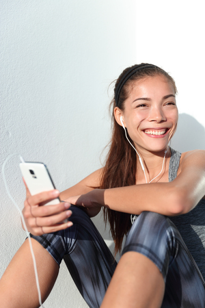 woman listening to music: Happy active girl listening to music on smartphone app phone lifestyle. Young female athlete getting ready for fitness workout or running by choosing song playlist on phone smiling. Stock Photo