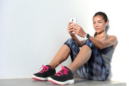 La deportista escuchar música mediante aplicación de teléfono y la actividad de la aptitud SmartWatch rastreador - monitor de frecuencia cardíaca seguimiento de su progreso de la salud en el teléfono inteligente. atleta asiático en ropa de moda de ropa deportiva.