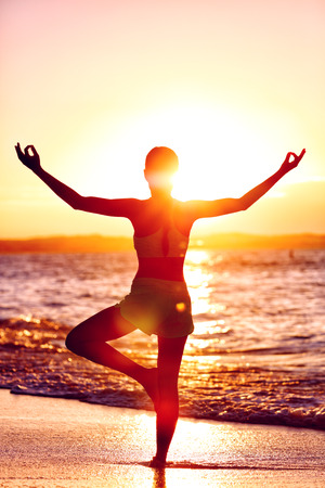 legs open: Wellness of mind - Yoga woman standing on one leg doing tree pose with open raised arms in sunset flare in front of the ocean on beach. Mindfulness and meditation concept. Stock Photo