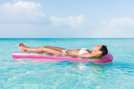 Strand sexy vrouw ontspannen tijdens het zonnen zonnebaden op drijvende pool roze opblaasbare plastic luchtmatras drijven in de ongerepte turquoise oceaanwater achtergrond bij luxe bestemming uitje.