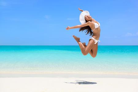 幸せなビキニ女性のビーチで喜びのジャンプします。興奮して休日女の子の自由と自由なボディで幸福のジャンプを行います。重量損失の成功健康
