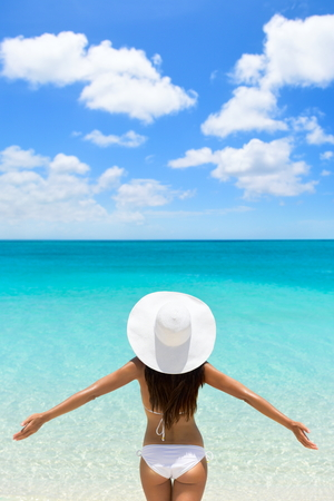 Happy beach vacation carefree woman on luxury tropical getaway destination wearing a white sun hat from behind with arms raised in freedom.  Person from behind with slim body. Happiness and success.