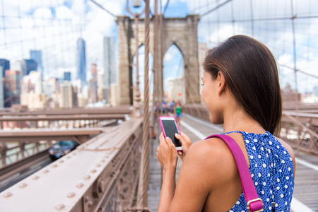 big apple: Smartphone texting girl on Brooklyn bridge in urban New York City, Manhattan USA. View from the back of unrecognizable business woman holding phone reading or using social media in summer.