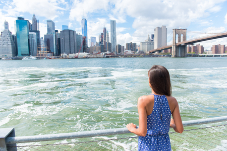 New York city urban woman enjoying view of downtown Manhattan skyline from Brooklyn park living a happy lifestyle walking during summer travel in USA. Female Asian tourist in her 20s. Stok Fotoğraf