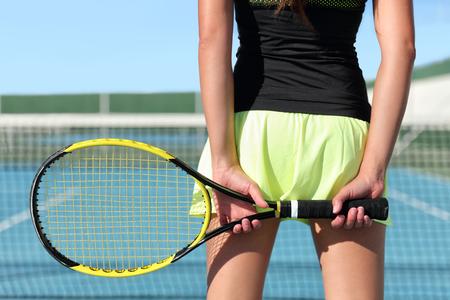 Tennisser bedrijf racket de voorbereiding voor het spelen game op buitenbaan tijdens de zomer. Close-up van de handen en sport rok met net op de achtergrond. Onherkenbaar onderlichaam van de persoon van de achterkant.
