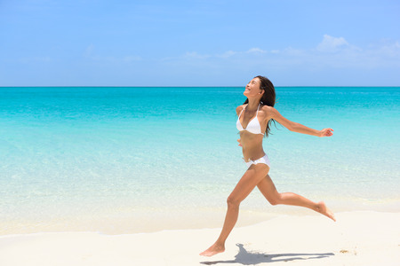 Beach bikini woman carefree running in freedom fun. Joyful happy Asian girl relaxing showing joy and happiness in slim body for weight loss diet concept on perfect white sand.
