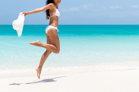 Beach ready bikini body - slim legs and toned thighs and butt. Suntan happy woman jumping in freedom on white sand with sun hat. Weight loss success or epilation concept.